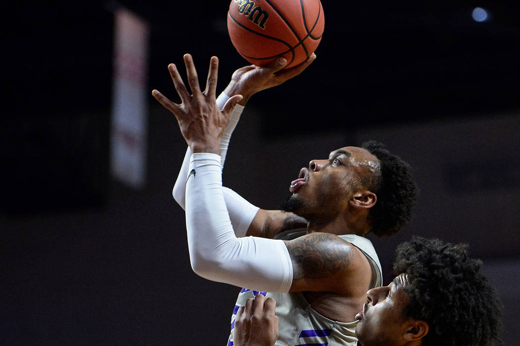 Grand Canyon guard Carlos Johnson (23) jumps up to take a shot while being guarded by Seattle guard/forward Riley Grigsby (35) in the first half of the opening round of the Western Athletic Confer ...