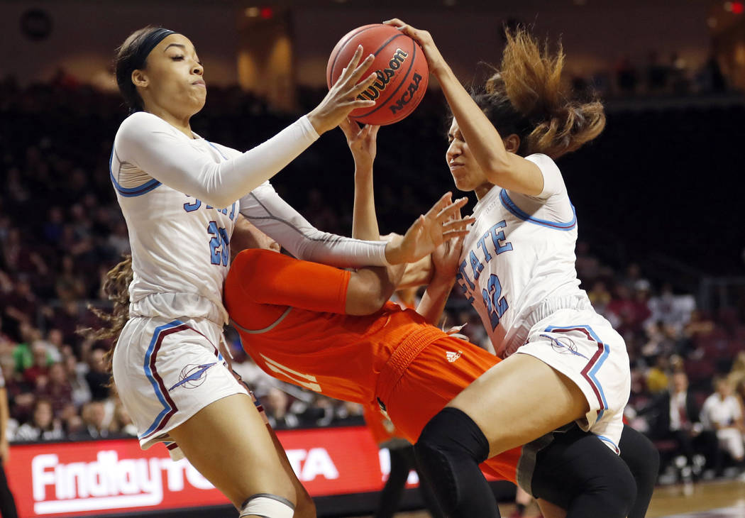 New Mexico State guard Dominique Mills, left, and teammate Kalei Atkinson (22) go after a loose ball over Texas-Rio Grande Valley guard Quynne Huggins (11) during an NCAA college basketball game i ...