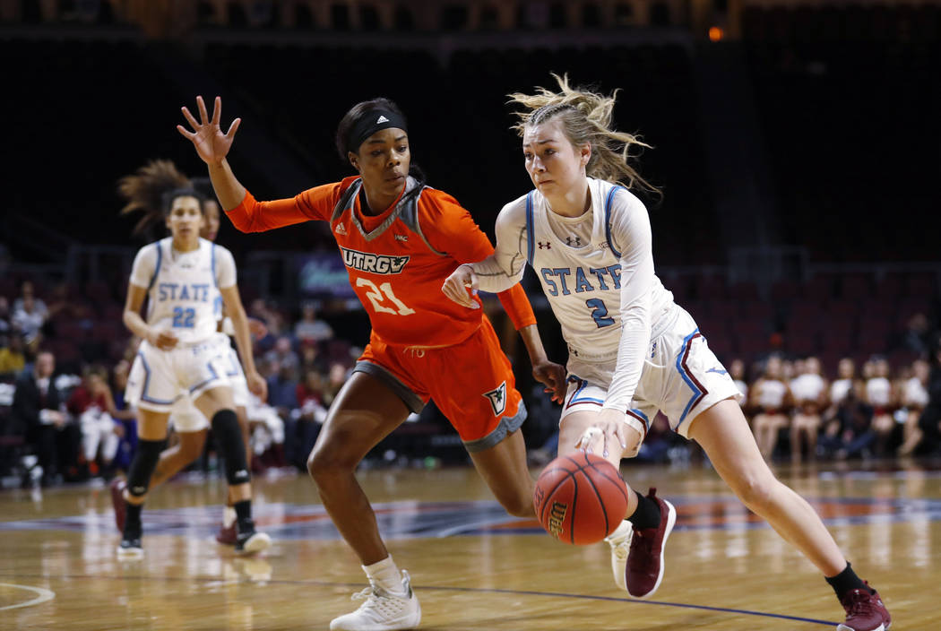 New Mexico State guard Brooke Salas (2) drives past Texas-Rio Grande Valley forward Krisynthia Sampson (21) during a NCAA college basketball Western Athletic Conference Women's Tournament champion ...