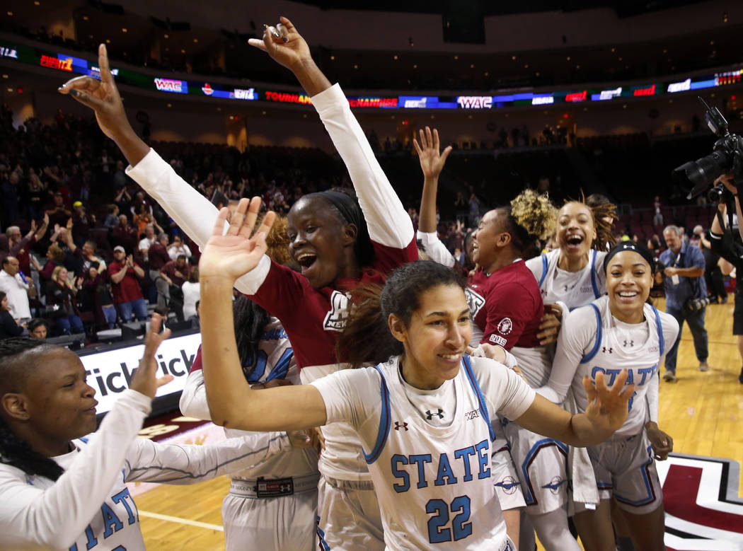 New Mexico State players celebrate after defeating Texas-Rio Grande Valley 76-73 in double overtime during a NCAA college basketball Western Athletic Conference Women's Tournament championship gam ...