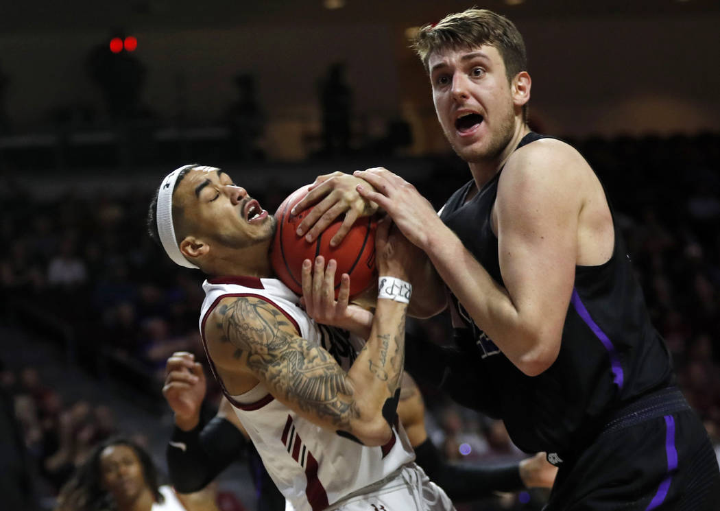 New Mexico State guard Trevelin Queen (20) and Grand Canyon's Alessandro Lever vie for a rebound during the first half of an NCAA college basketball game for the Western Athletic Conference men's ...