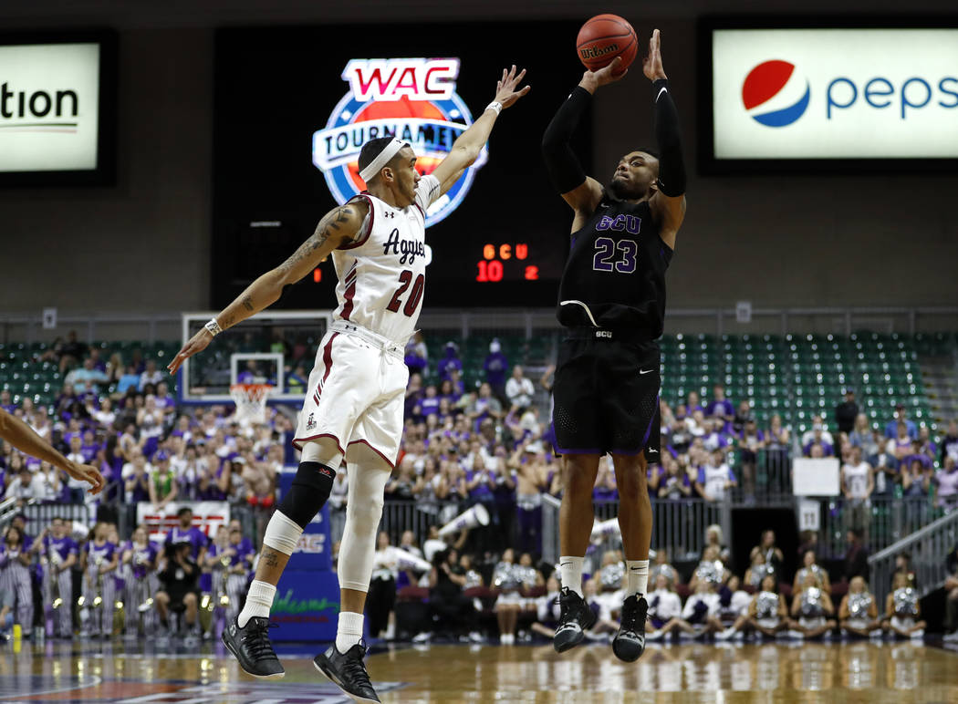 Grand Canyon's Carlos Johnson (23) shoots over New Mexico State guard Trevelin Queen (20) during an NCAA college basketball game for the Western Athletic Conference men's tournament championship S ...