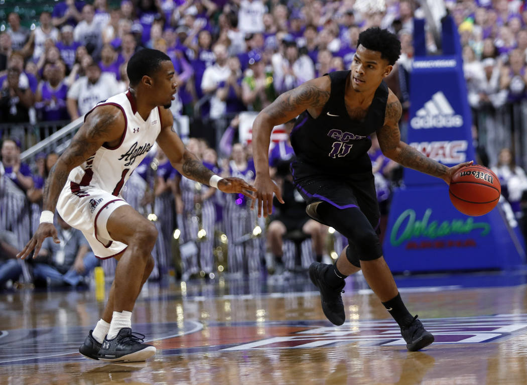 Grand Canyon's Damari Mislead (11) drives by New Mexico State guard AJ Harris (12) during the first half of an NCAA college basketball game for the Western Athletic Conference men's tournament cha ...