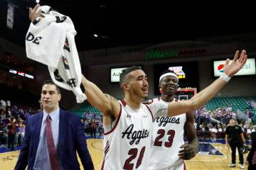 New Mexico State guard Trevelin Queen (20) and forward Mohamed Thiam (23) celebrate the team's 89-57 win over Grand Canyon in an NCAA college basketball game for the Western Athletic Conference me ...