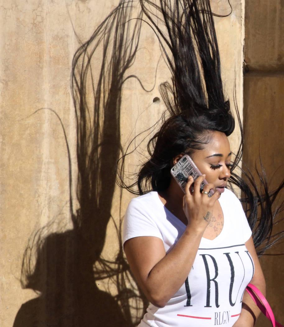 A woman has her hair blown by heavy wind as she talks on her phone on Third street on Wednesday, March. 13, 2019, in Las Vegas. Bizuayehu Tesfaye Las Vegas Review-Journal @bizutesfaye