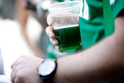 A reveler holds green beer at the Fremont Street Experience in downtown Las Vegas on Sunday, March 17, 2013. (Las Vegas Review-Journal/file)