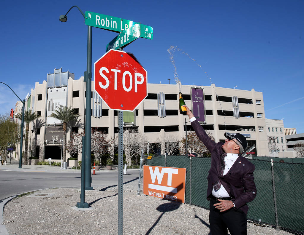 Larry Ruvo uses champagne to christen Robin Leach Lane running between the Cleveland Clinic Lou Ruvo Center for Brain Health and The Smith Center for the Performing Arts in Las Vegas Friday, March ...