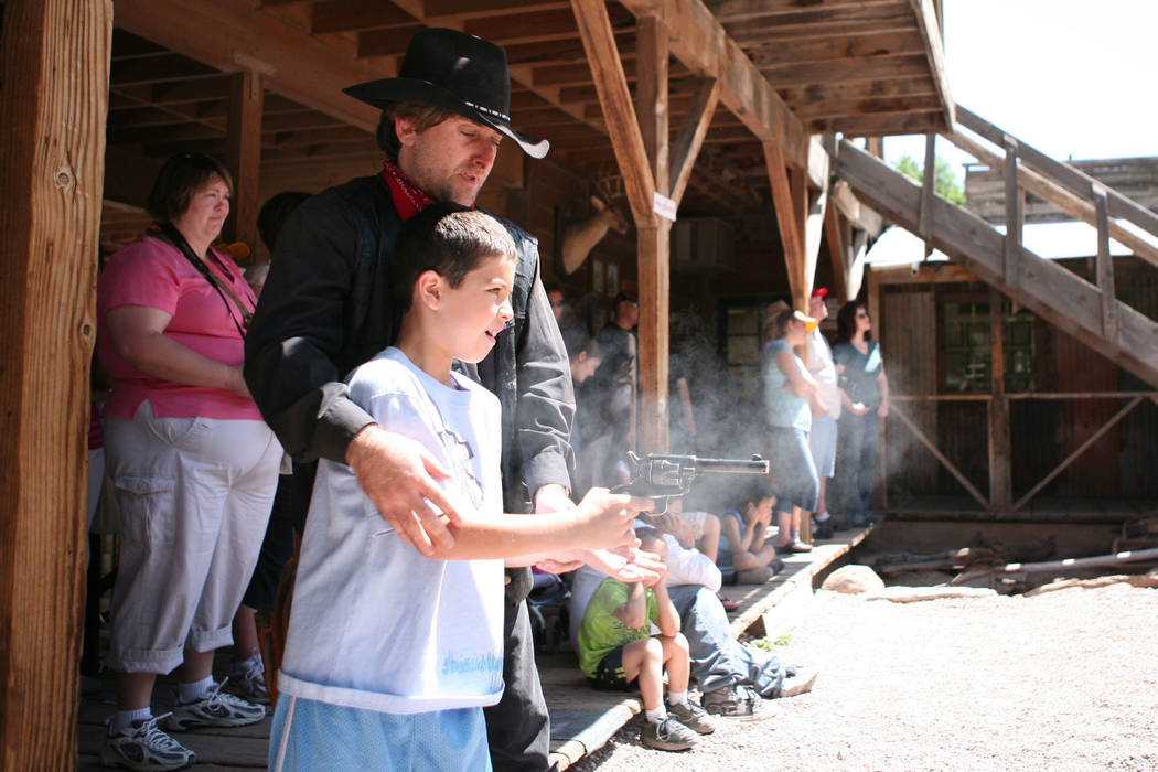 Former Las Vegas Review-Journal columnist Corey Levitan, left, teaches 9-year-old Lennon Walker how to use the .22 caliber prop gun at Bonnie Springs on April 28, 2007. (Las Vegas Review-Journal file)