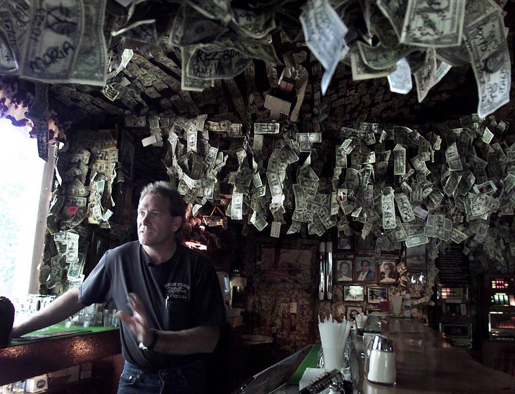 Alan Levinson stands behind the bar of the Bonnie Springs Ranch in 2001. The bar wall is covered with thousands of dollar bills left by visitors. The Levison family are going to take down the mone ...