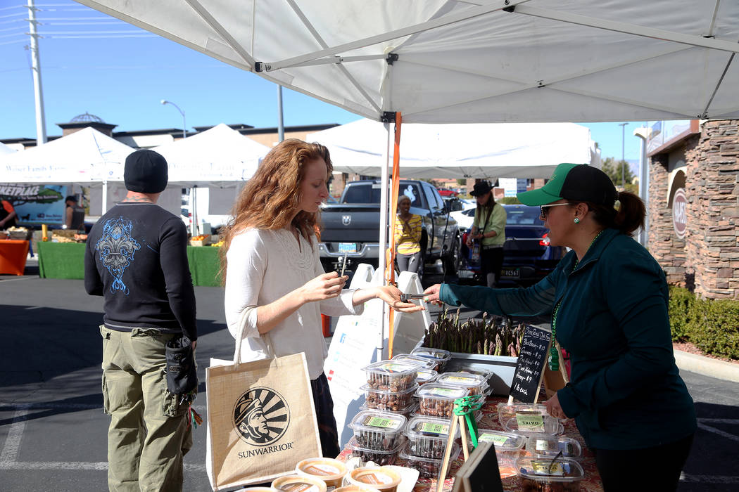 Carrie Hogan, founder of the Fresh52 farmers and artisans market, gives Sydney Ramsdell a sample of dates from China Ranch Date Farm at the Fresh52 farmers and artisans market in Las Vegas, Sunday ...