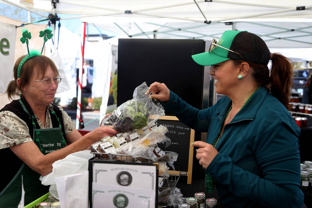 Diane Greene shows Carrie Hogan, founder of the Fresh52 farmers and artisans market, a sample of mustard greens at her booth Herbs by Diane at the Fresh52 farmers and artisans market in Las Vegas, ...