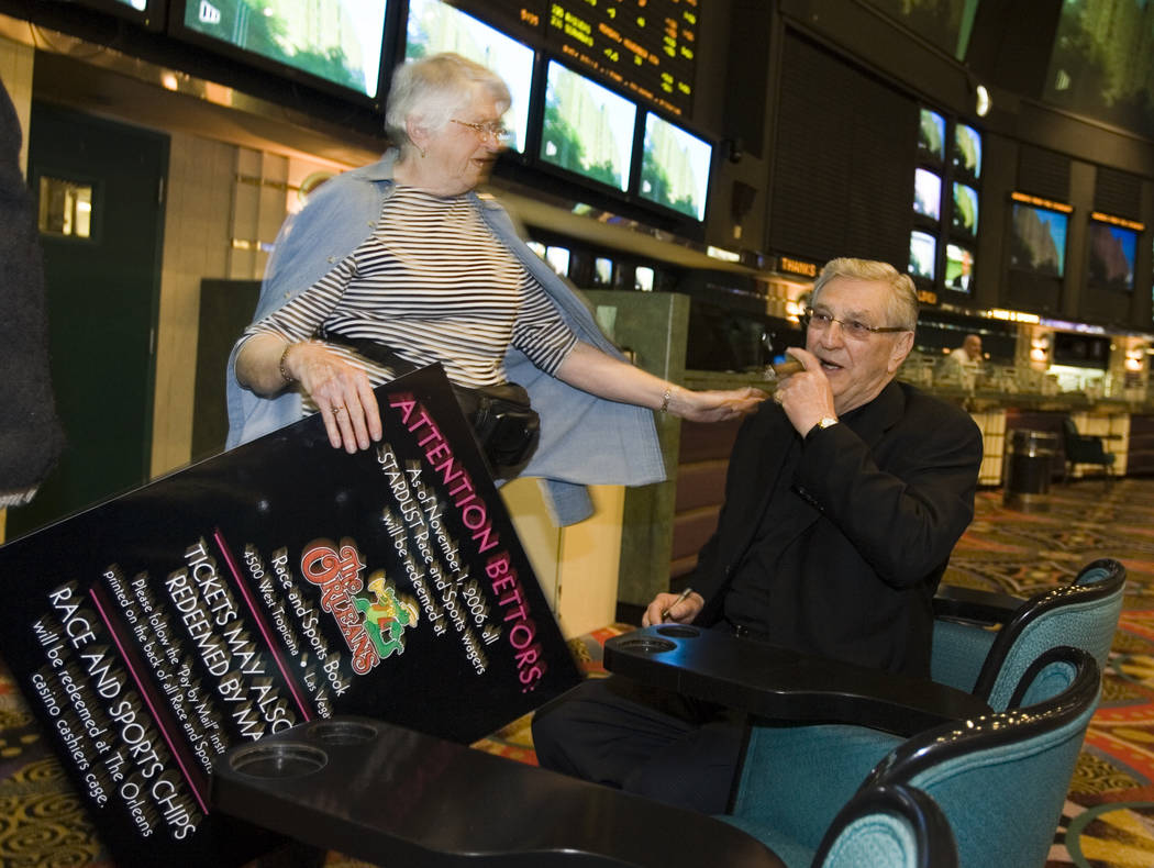 Twenty year patron Joyce Lindsay from Manitoba, Canada asks Bill Boyd, chairman of Boyd Gaming, to autograph a souvenir sign in the Stardust Race and Sports book shortly before the resort closed ...
