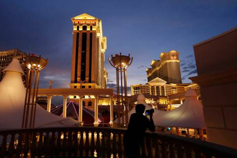 A man takes pictures of Caesars Palace in Las Vegas. (AP Photo/John Locher)