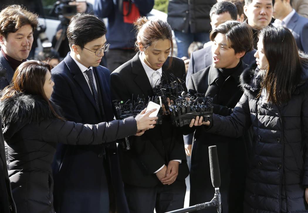 K-pop singer Jung Joon-young, center, arrives at the Seoul Metropolitan Police Agency in Seoul, South Korea, Thursday, March 14, 2019. Police have alleged Jung secretly filmed himself having sex w ...