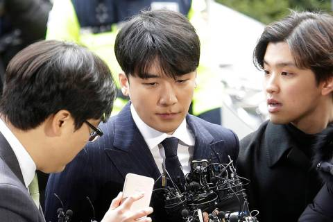 Seungri, center, member of a popular K-pop boy band Big Bang, arrives at the Seoul Metropolitan Police Agency in Seoul, South Korea, Thursday, March 14, 2019. After their stunning retirement annou ...