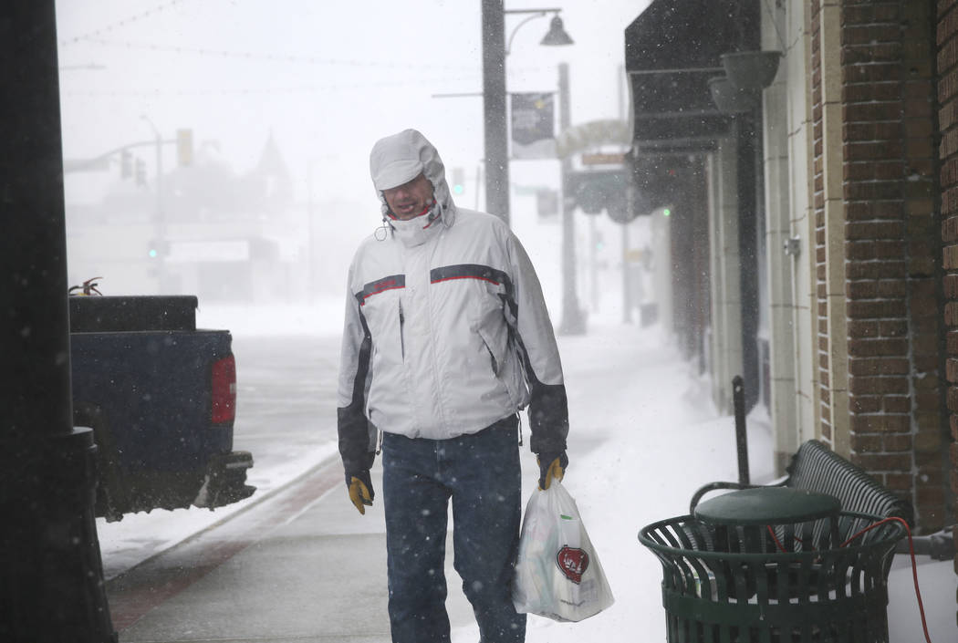 A man walks along 17th Street during a blizzard on Wednesday, March 13, 2019, in Cheyenne. White-out conditions closed I-80, I-25, and U.S. 85, effectively closing off the state capital from Nebra ...