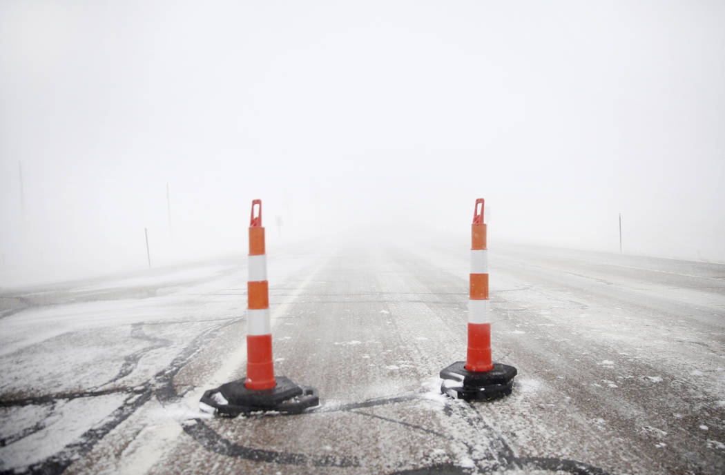 Cones block travel on Happy Jack Road during a blizzard on Wednesday, March 13, 2019, in Cheyenne, Wyo. White-out conditions closed I-80, I-25, and U.S. 85, effectively closing off the state capit ...