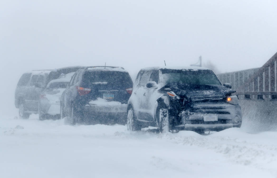A string of wrecked vehicles sit on an overpass over Interstate 70 as a late winter storm packing hurricane-force winds and snow sweeps over the intermountain West Wednesday, March 13, 2019, in Au ...