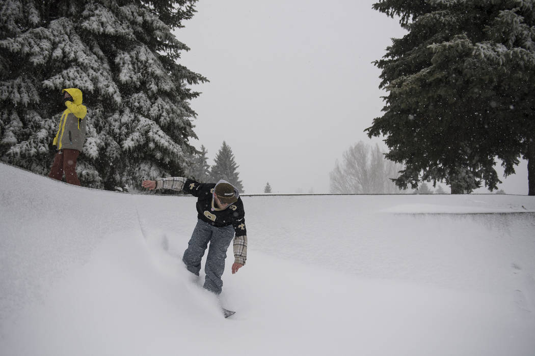 Bobby Larson drops into the bowl on a snowboard in Edora Park on Wednesday, March 13, 2019, in Fort Collins, Colo. A winter storm hit the western U.S., with blizzard conditions expected to engulf ...