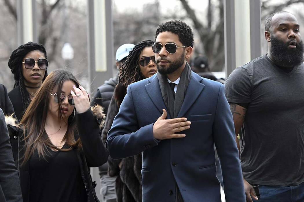 """""""Empire"""" actor Jussie Smollett, center, arrives at the Leighton Criminal Court Building for his hearing on Thursday, March 14, 2019, in Chicago. Smollett is accused of lying to police about being ..."""