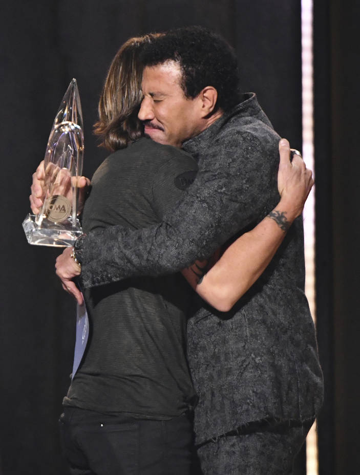 Lionel Richie, right, embraces Keith Urban, winner of the award for entertainer of the year at the 52nd annual CMA Awards at Bridgestone Arena on Wednesday, Nov. 14, 2018, in Nashville, Tenn. (Cha ...