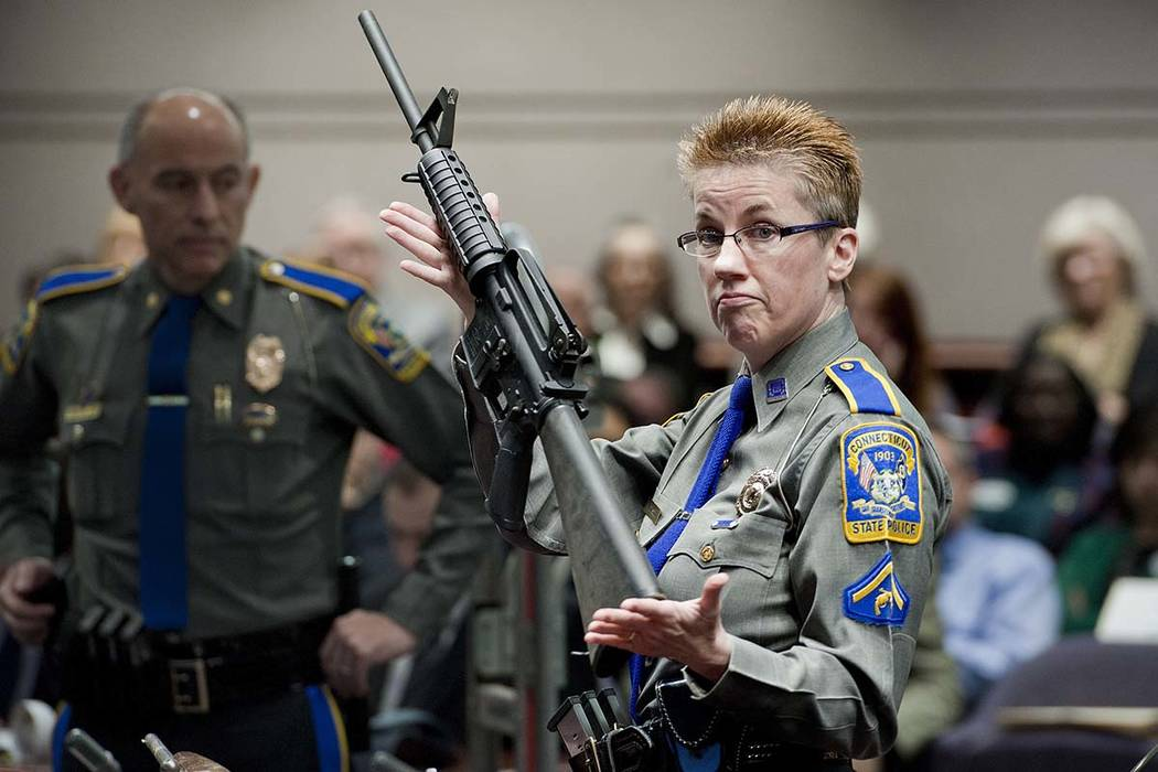 In this Jan. 28, 2013, file photo, firearms training unit Detective Barbara J. Mattson, of the Connecticut State Police, holds a Bushmaster AR-15 rifle, the same make and model used by Adam Lanza ...