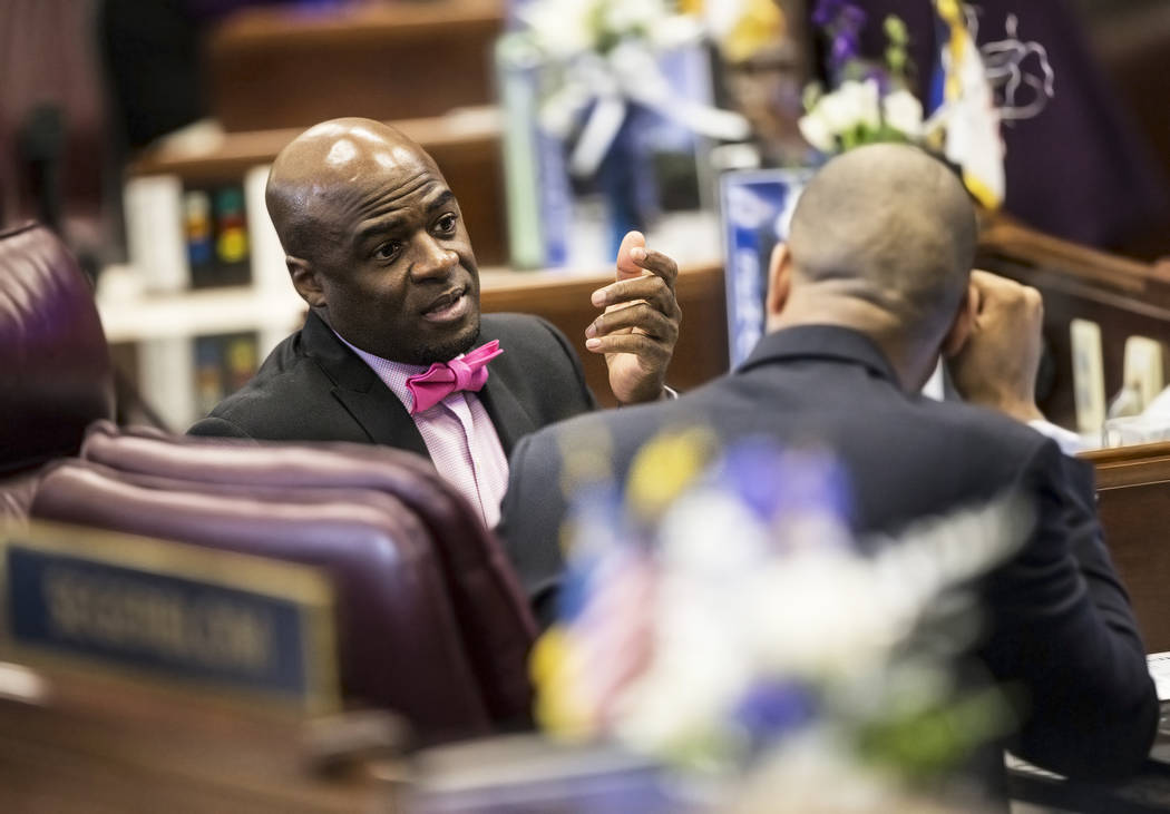 Sen. Kelvin Atkinson, D-North Las Vegas, left, speaks with Senate Majority Leader Aaron Ford, D-Las Vegas, in the Senate Chambers during the third day of the Nevada Legislative session on Wednesda ...