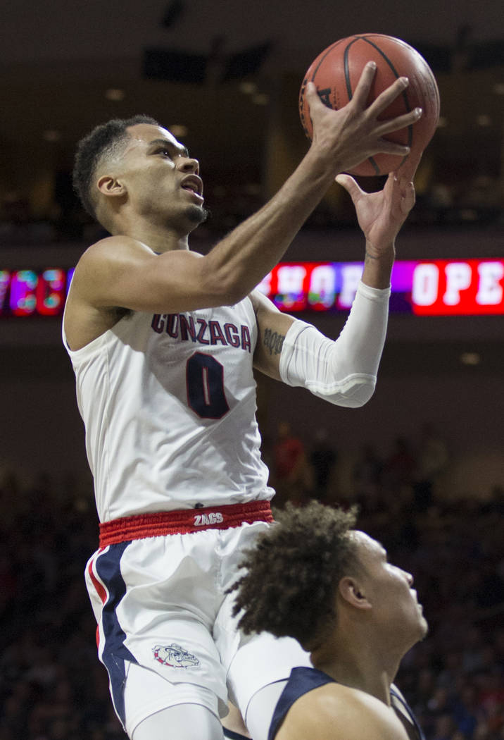 Gonzaga senior guard Geno Crandall (0) slices to the rim past Pepperdine sophomore guard Colbey Ross (4) in the first half during the West Coast Conference semifinal game on Monday, March 11, 2019 ...