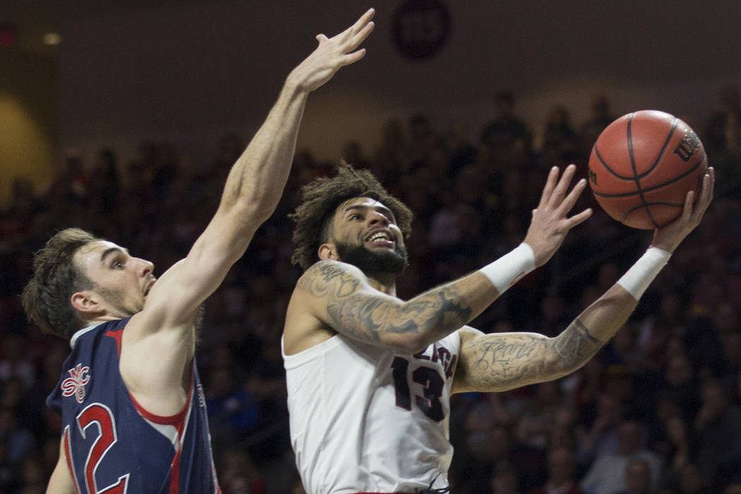 Gonzaga senior guard Josh Perkins (13) slices to the rim past Saint Mary'ssophomore guard Tommy Kuhse (12) in the first half during the West Coast Conference finals game on Tuesday, March 12 ...