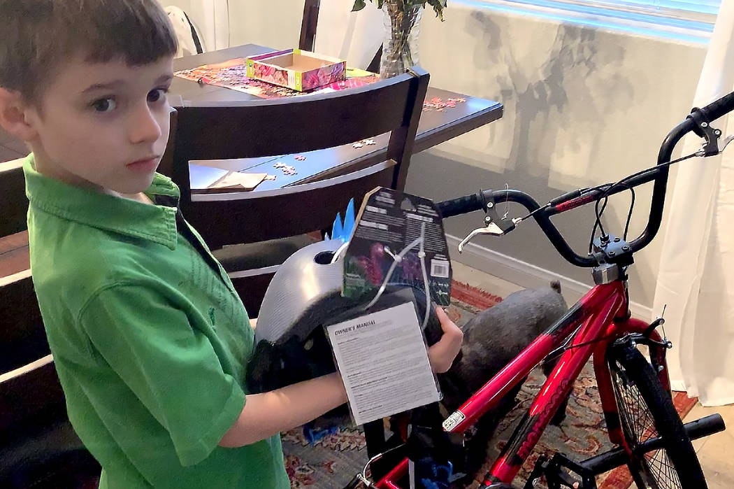 Spencer Powell, 8, shows the new bicycle and helmet he received from an anonymous donor after his accident. (Mat Lusheck/Las Vegas Review-Journal)