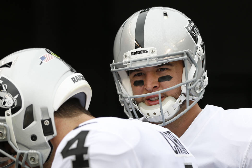 Oakland Raiders quarterback AJ McCarron, right, prepares to take the field during practice before an NFL football game, Sunday, Dec. 16, 2018, in Cincinnati. (AP Photo/Frank Victores)