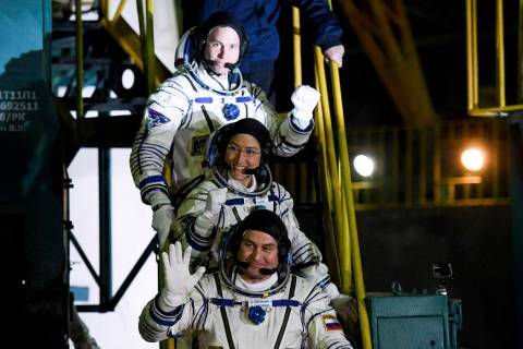 U.S. astronauts Christina Hammock Koch, centre, Nick Hague, above, and Russian cosmonaut Alexey Ovchinin, crew members of the mission to the International Space Station, ISS, wave as they board to ...