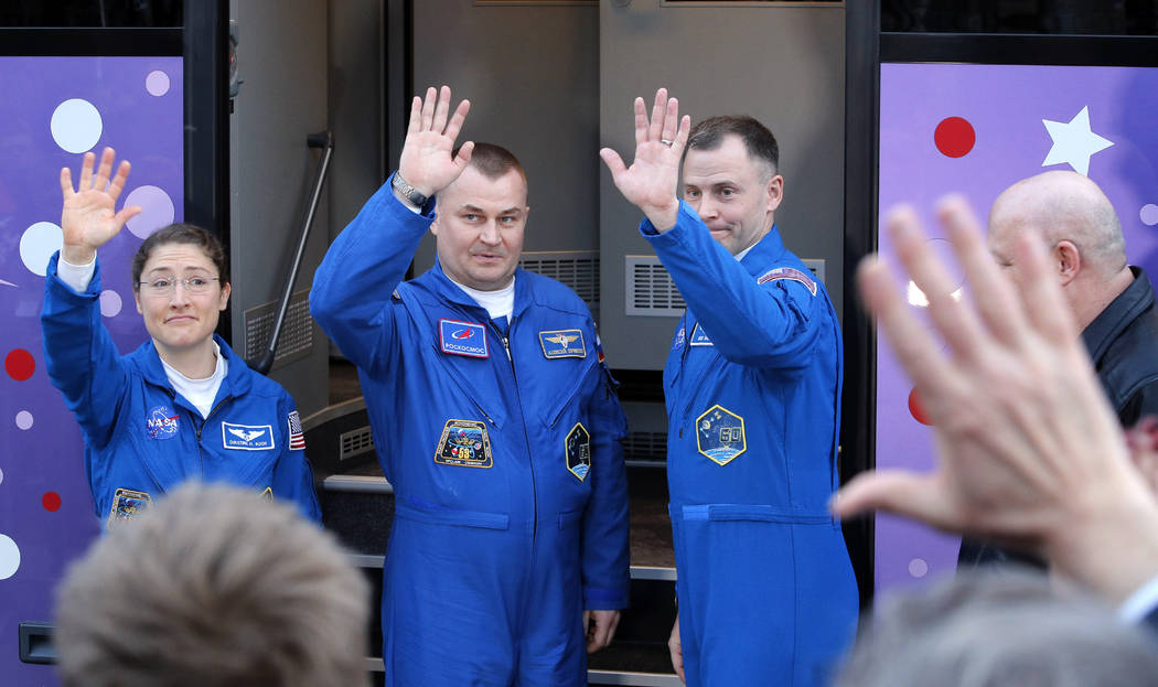 U.S. astronauts Christina Hammock Koch, left, Nick Hague, right, and Russian cosmonaut Alexey Ovchinin, members of the main crew to the International Space Station (ISS), pose near a bus prior to ...