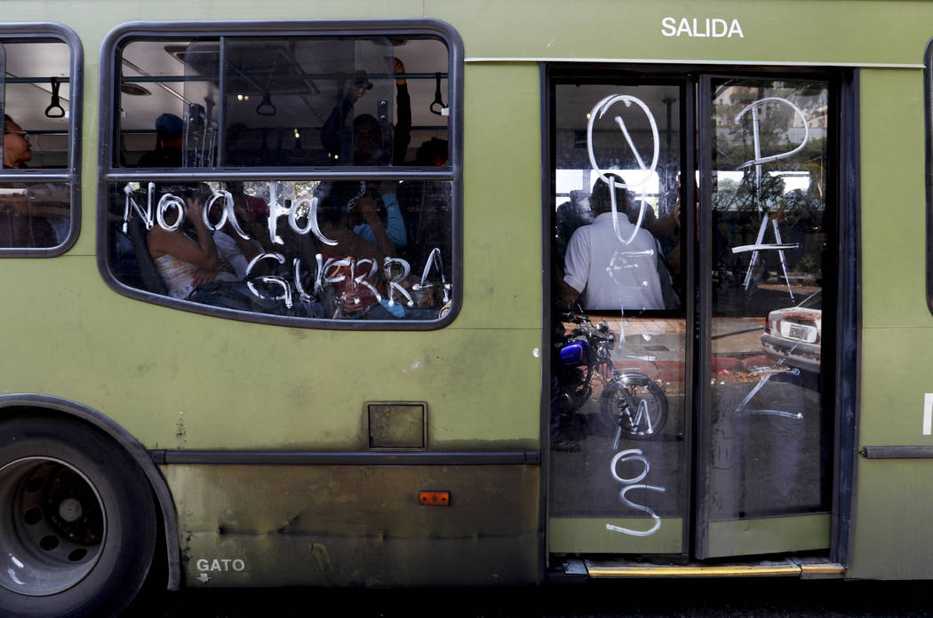 """Passengers ride on a bus with messages scrawled on it that read in Spanish """"No to war,"""" and """"We want peace,"""" in Caracas, Venezuela, Thursday, March 14, 2019. With long lines at ..."""
