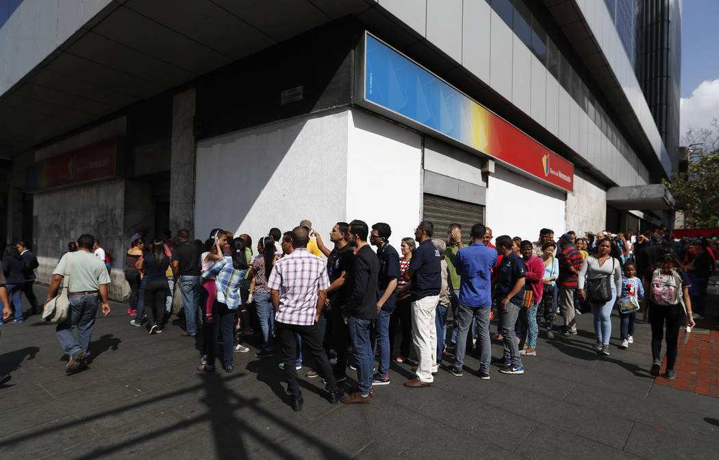 People line up outside a bank in Caracas, Venezuela, Thursday, March 14, 2019. With long lines at the stops of public transport and crowds of people at the entrance of some banking agencies, Venez ...