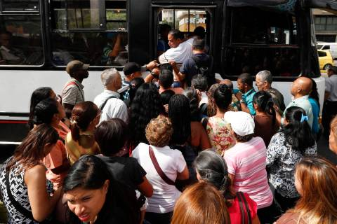 Passengers scramble to board a bus in Caracas, Venezuela, Thursday, March 14, 2019. With long lines at the stops of public transport and crowds of people at the entrance of some banking agencies, ...
