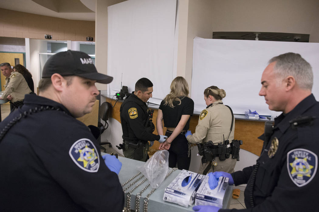 "Marshal Johnny Patino, second from left, and Metro Officer B. Muenzenmeyer, second from right, process a suspected impaired driver at the Metro Traffic Bureau as part of a ""DUI blitz"" on ..."