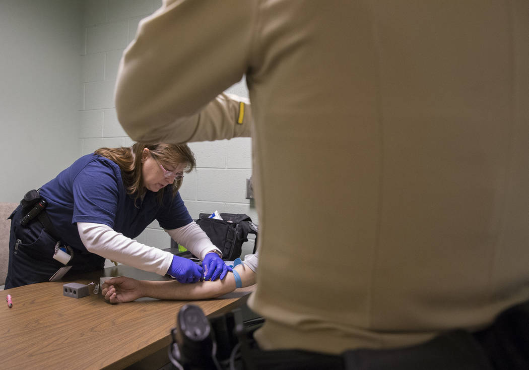 "EMT Katharine York, left, draws blood from a suspected impaired driver at the Metro Traffic Bureau as part of a ""DUI blitz"" on Thursday, March 14, 2019, in Las Vegas. (Benjamin Hager Rev ..."