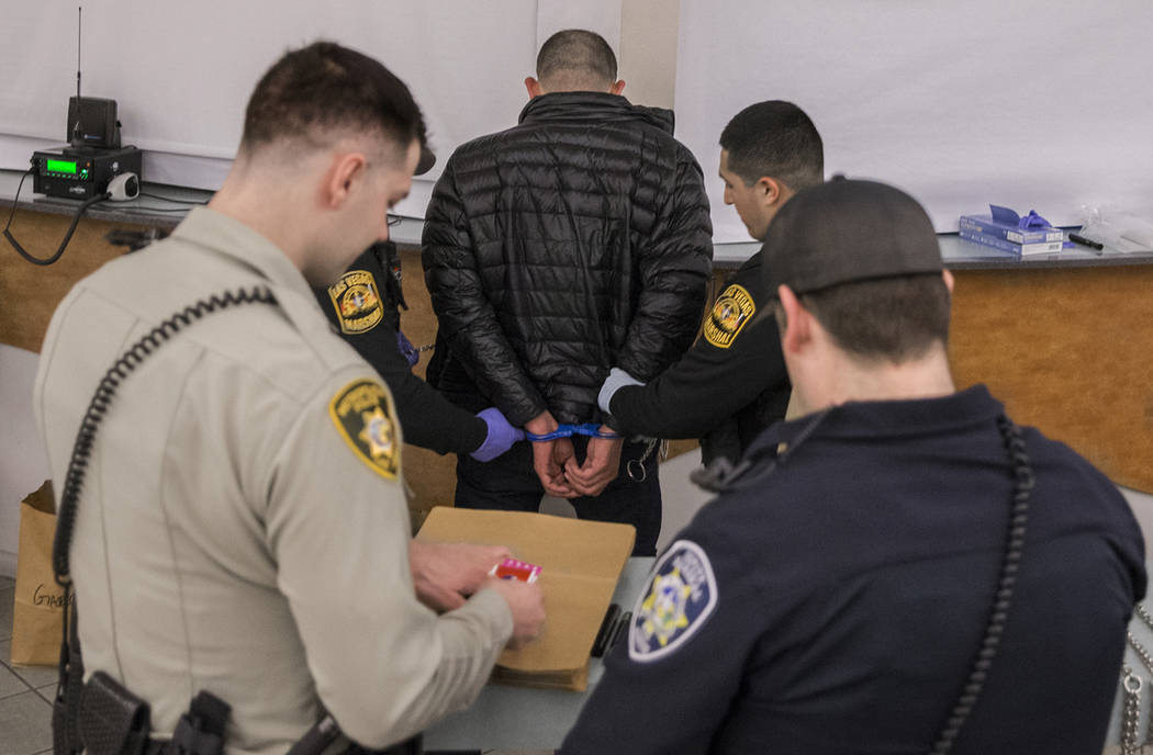 "A suspected impaired driver, middle, is processed by Las Vegas Marshals at the Metro Traffic Bureau as part of a ""DUI blitz"" on Thursday, March 14, 2019, in Las Vegas. (Benjamin Hager Re ..."