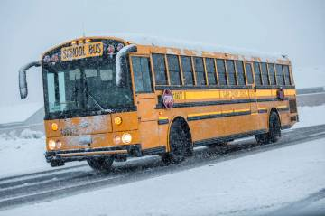 School buses make their way through heavy snow to Centennial High School on Thursday, Feb. 21, 2019, in Las Vegas. (Benjamin Hager Review-Journal) @BenjaminHphoto