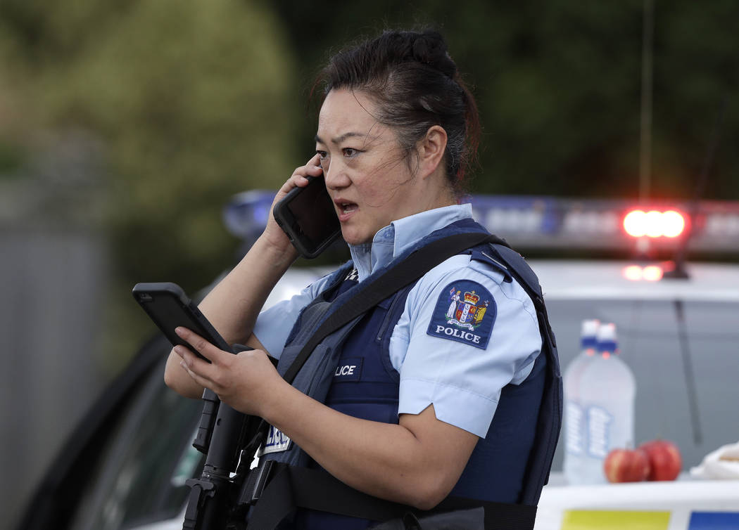 A police officer talks on her phone as a roadblock near a mass shooting at a mosque in Linwood, Christchurch, New Zealand, Friday, March 15, 2019. Multiple people were killed during shootings at t ...