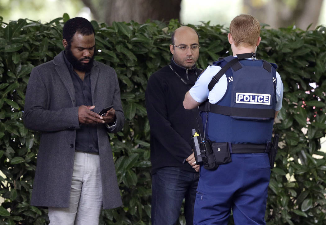 A police officer photographs witnesses near a mosque in central Christchurch, New Zealand, Friday, March 15, 2019. Multiple people were killed in mass shootings at two mosques full of people atten ...