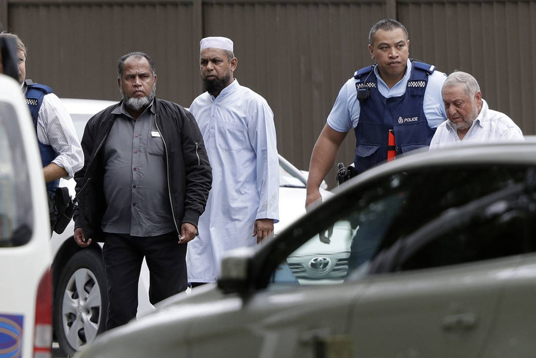 Police escort men from a mosque in central Christchurch, New Zealand, Friday, March 15, 2019. (AP Photo/Mark Baker)
