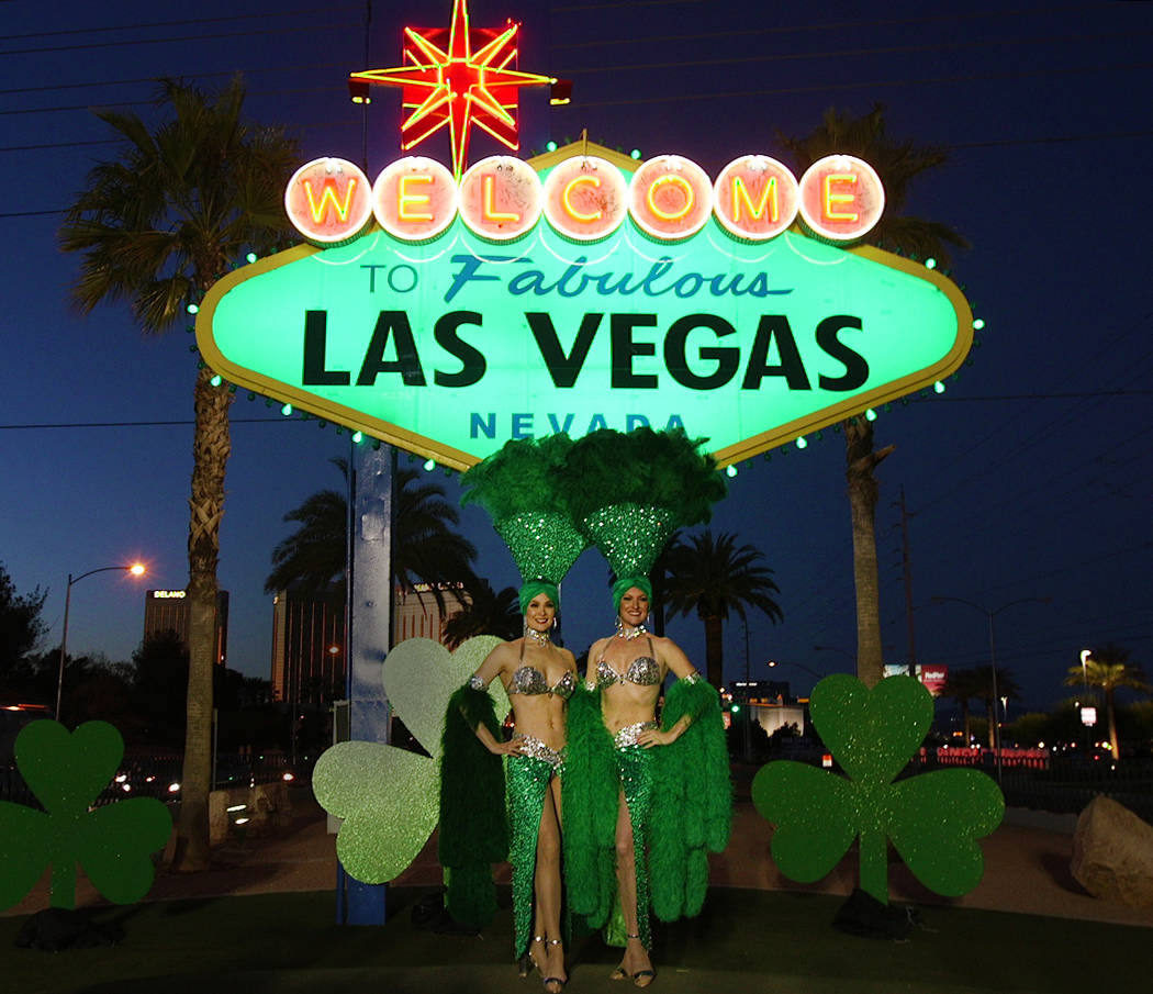 """Showgirls pose in front of the """"Welcome to Fabulous Las Vegas"""" sign on Thursday, March 14, 2019. The sign was lit green in celebration of St. Patrick's Day. (Mat Luschek/Las Vegas Review-Journal)"""