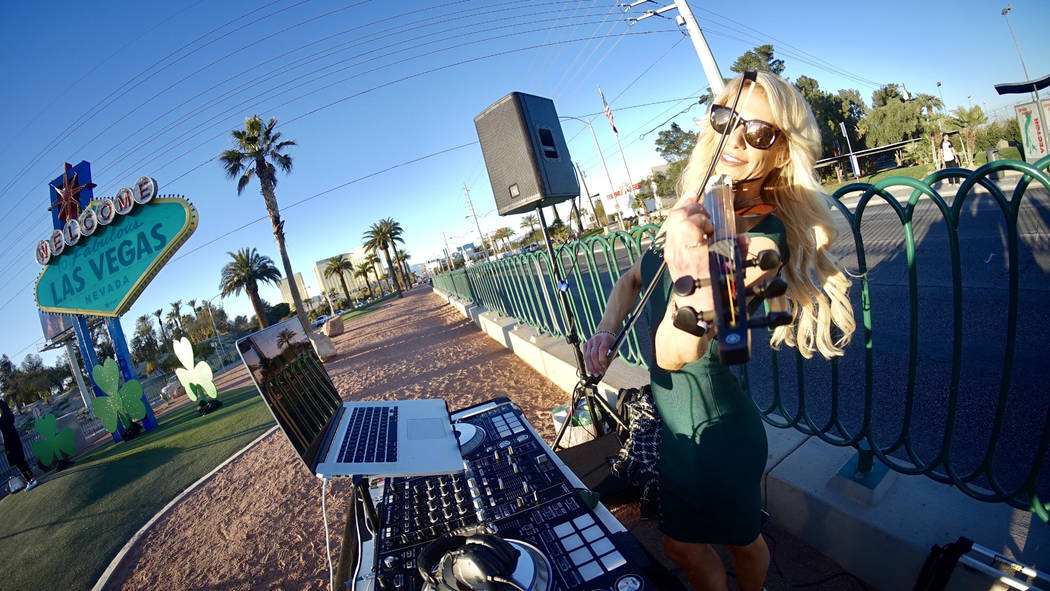 """DJ/violinist Lydia Ansel plays the violin in front of the """"Welcome to Fabulous Las Vegas"""" sign on Thursday, March 14, 2019. The sign was lit green in celebration of St. Patrick's Day. (Mat Luschek ..."""