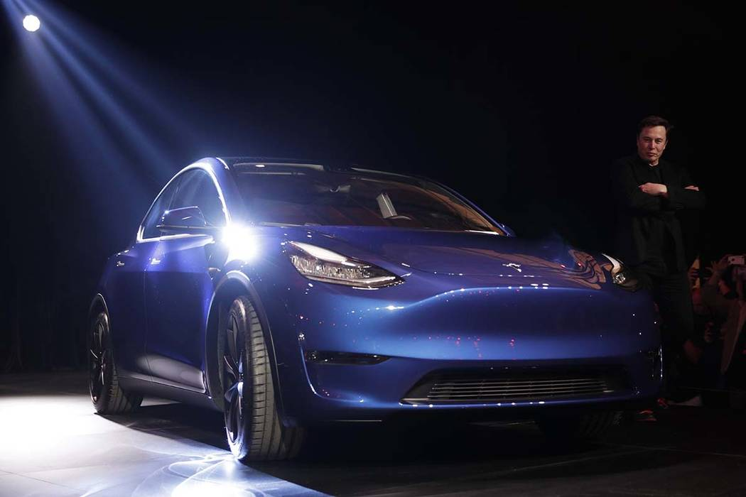 Tesla CEO Elon Musk, right, stands next to the Model Y at Tesla's design studio Thursday, March 14, 2019, in Hawthorne, Calif. The Model Y may be Tesla's most important product yet as it attempts ...