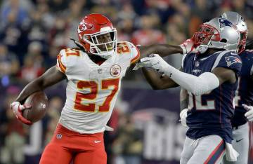 Kansas City Chiefs running back Kareem Hunt (27) gives a stiff arm to New England Patriots defensive back Devin McCourty (32) as he runs for yardage during the first half of an NFL football game, ...