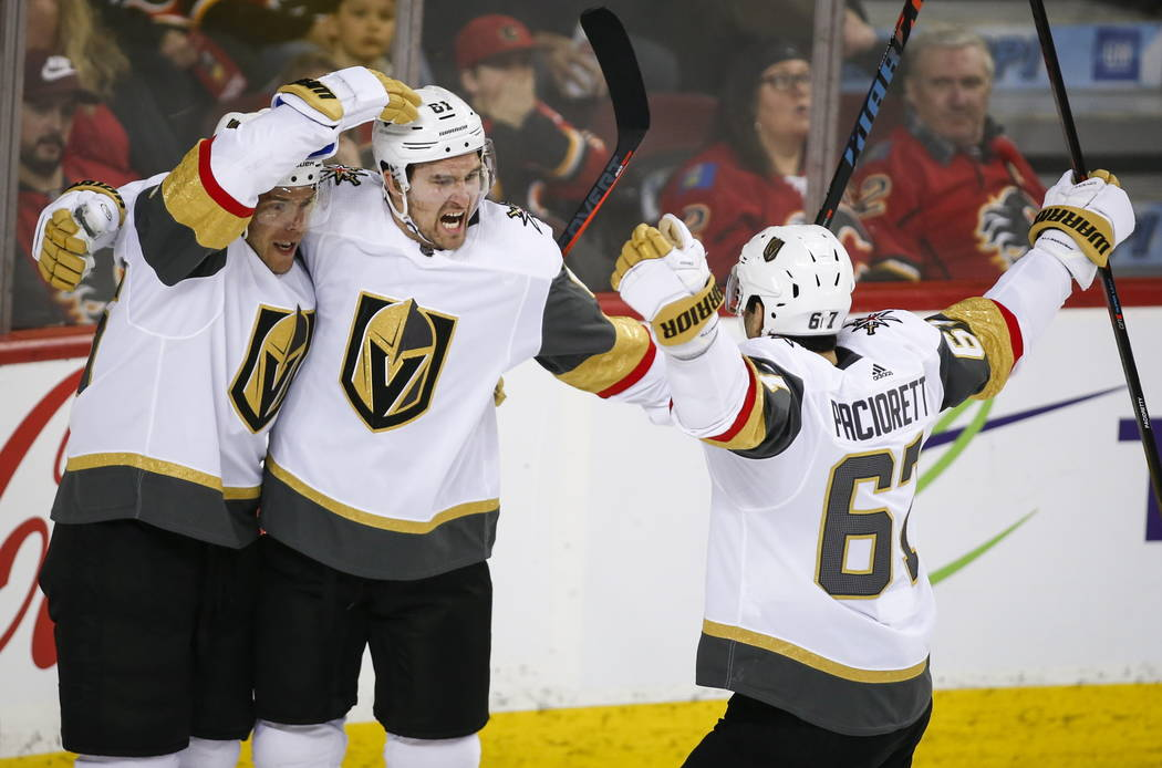 Vegas Golden Knights' Mark Stone, center, celebrates his goal with teammates during second period NHL hockey action against the Calgary Flames in Calgary, Alberta, Sunday, March 10, 2019. (Jeff Mc ...