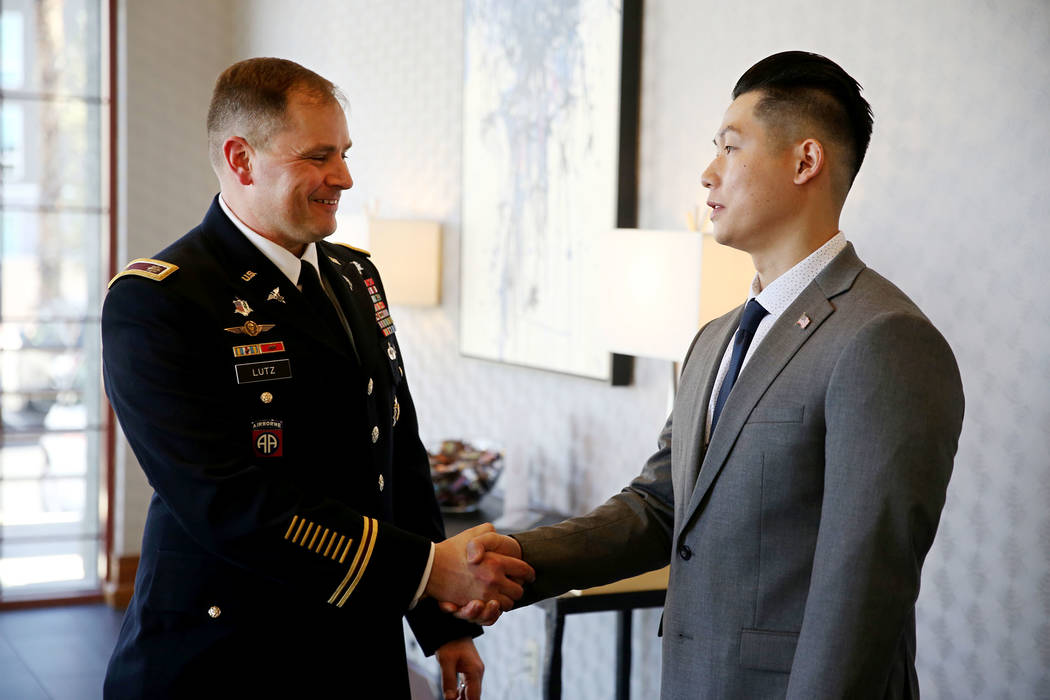 U.S. Army battalion commander Ken Lutz of the 6th Medical Recruiting Battalion, left, congratulates Anthony Hua after getting sworn in as captain for the U.S. Army Reserve during a ceremony at the ...