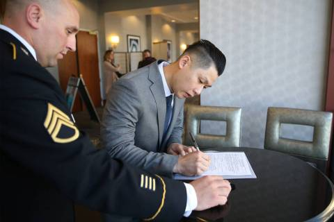 Anthony Hua, right, with U.S. Army Staff Sgt. Zachary Anderson, a health care recruiter, signs his contract after getting sworn in as U.S. Army Reserve captain during a ceremony at the Hampton In ...